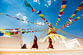 Buddhist monks walking around stupa at Bouddha (Boudhanath temple, UNESCO World Heritage Site, Kathmandu, Nepal, Asia