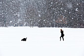 Woman walking her dog during Snow Fall, English Garden, Munich, Germany