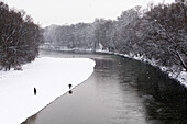 Walking at the river Isar during snow fall, Munich, Germany