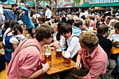 Young people in traditional cloth with beer mugs to toast at Oktoberfest, Munich, Bavaria, Germany