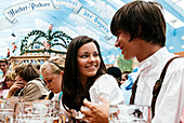Young man and woman in traditional cloth in beer tent at Oktoberfest, Munich, Bavaria, Germany