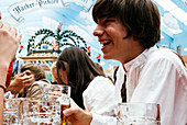 Young laughing man in traditional cloth in beer tent at Oktoberfest, Munich, Bavaria, Germany