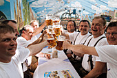 Middle-aged men raise their beer mugsto toast at Oktoberfest, Munich, Bavaria, Germany