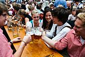 Revelers raise their beer mugs to toast at Oktoberfest, Munich, Bavaria, Germany