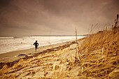 A female athlete on a cold weather training run along the beach of Hull, MA.