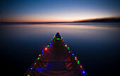 A canoe with two strands of led christmas lights attached to the rails. Shot on Lake Monona in Madison, WI during the month of December.