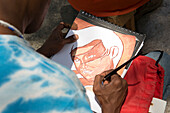 A young male Cuban street artist paints a watercolor of a girl's face on a sketchpad, as seen over his shoulder. Artist work and sell their art on El Prado Boulevard (Paeeo Marti) as families stroll on Sundays.  Centro Havana, La Habana, Cuba