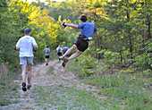 People Running On Trail In Forest