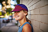 Close-up Of Smiling Female Athlete Leaning On Wall