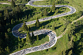 Aerial view of the road up to Passo Pordoi (2239 m), the second pass of the Maratona dles Dolomites bikerace. The race is held once a year in July with up to 8500 cyclists competing, from amateurs to professionals. Dolomites, Italy.