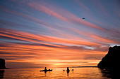 Loreto, Baja California Sur, Mexico. A couple relax in their sea kayaks watching an amazing orange blue sky at sunrise off the coast of Loreto, Baja California Sur, Mexico.