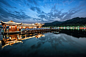 Dramatic sky at West Lake with reflections, pagoda-ship and boats