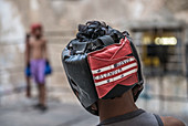 'Closeup of a the head and headgear of a young Cuban boy as he prepares to spar with his opponent seen in the background at Project Cuba Boxeo, an aid project from Malaika Aid for Children, the creation of Samuel 'Sammy' Fabbri. The organization brings bo
