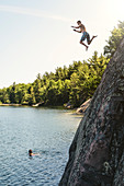 A Young Man Is Jumping Off A Cliff Into George Lake While Another Person Is Looking From Under