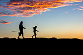 Silhouette Of Father And Daughter Head Out On A Jetty To Go Fishing