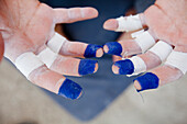 Close Up Of A Climber's Hands With Fingertips Wrapped In Blue Colored Tape
