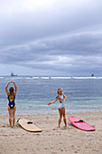 Two Young Women Stretch And Flex Before Surfing At Beach