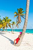 Canto de la Playa, Saona Island, Ost-Nationalpark, Parque Nacional del Este, Dominikanische Republik, Karibisches Meer, Schöne Frau mit roten Sarong Entspannung am Palmen gesäumten Strand, MR