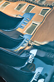 Europe, Italy, Veneto, Venice,  Abstract view of gondolas traditional prows and buildings reflected on the water