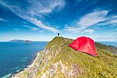Tent and hiker on mountain ridge overlooking the sea Sorland Vaeroy Island Nordland county Lofoten archipelago Norway Europe