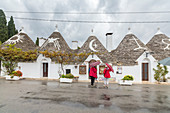 Tourists admire the typical Trulli built with dry stone with a conical roof Alberobello province of Bari Apulia Italy Europe
