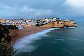 View of Carvoeiro village surrounded by sandy beach and clear sea at dusk Lagoa Municipality Algarve Portugal Europe