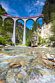 The alpine stream frames the Bernina Express train on Landwasser Viadukt Filisur Albula Valley Canton of Graubünden Switzerland Europe