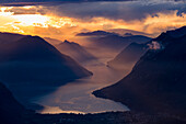 Sunset closing in on the mountains and the beautiful Glacial Lake Lugano, Switzerland
