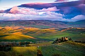 San Quirico d'Orcia, Tuscany, Italy Sunset over the valley with some farmhouses and a very cloudy sky