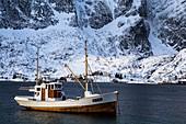 Norwegian fishing boat sailing through the seas of the Lofoten islands , Moskenes, Norway