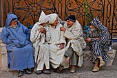 Old local men dressed with chilabas or djellabas (bereber clothes) at the heart of the central square, Outa el Hammam, Chefchaouen or Chaouen, Rif Region, Morocco, North Africa