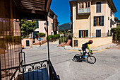 View from the historical train between Sóller and Palma on a street with one of many racing cyclists, Bunyola, Mallorca, Spain