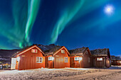The Northern Lights (aurora borealis) and moon light up typical wood huts called Rorbu, Manndalen, Kafjord, Lyngen Alps, Troms, Norway, Scandinavia, Europe