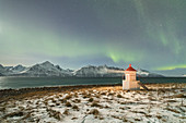 The Northern Lights (aurora borealis) and stars illuminate the lighthouse framed by icy sea, Djupvik, Lyngen Alps, Troms, Norway, Scandinavia, Europe