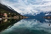 Das Dorf Muo, das Kotor über die Bucht, die Berge bedeckt in der niedrigen Wolke, Montenegro, Europa