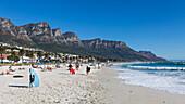 Skimboarder warten auf eine Welle an einem sonnigen Tag am Camps Bay Strand, Kapstadt, Western Cape, Südafrika, Afrika