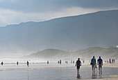 People enjoying walking on the main beach and in the sea in the late afternoon light, Hermanus, South Africa, Africa