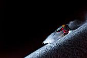 Man skiing in Rocky Point in Alta Ski Resort at night