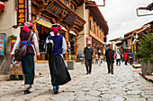 'An ancient street from Shangrila's old town, two women from a minority group walking; Shangri-La, Yunnan province, China'
