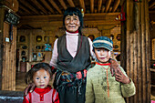 'Inside a traditional Tibetan house, big living room where an old woman and her grandsons pose for a photo; Daocheng, Sichuan province, China'