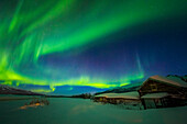 'The aurora fills the sky above the historic Black Rapids Roadhouse along the Richardson Highway on a bitterly cold night; Alaska, United States of America'