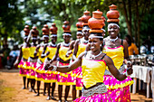 'Women wearing brightly coloured traditional clothing walk in a row and carry pottery on their heads; Uganda'