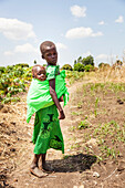 'A young girl carries a baby on her back in a sling; Uganda'