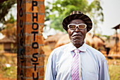 'A man with white eyeglasses stands posing outside a photo studio; Uganda'