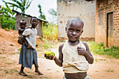 'A young child stands holding a piece of fruit with a girl holding a young child on her back in the background; Uganda'