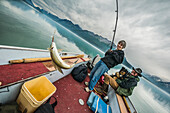 A woman catches a greyling from a small boat while her husband and dog watch, Lake Clark National Park & Preserve, Southcentral Alaska, USA