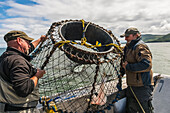 Two men prepare to drop a crab pot baited with halibut in the Cook Inlet near Kukak Bay, Katmai National Park & Preserve, Southwest Alaska, USA