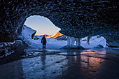 'A man walks out the entrance of an ice tunnel at the terminus of Canwell Glacier in the Alaska Range in mid-winter; Alaska, United States of America'