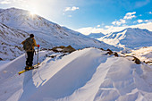 'A backcountry skier looks over the Black Rapids Glacier valley from a high point on the terminal moraine in winter; Alaska, United States of America'