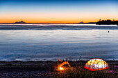 Lit tent and campfire on the beach at twilight, Hesketh Island, Homer, Southcentral Alaska, USA